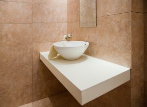 Decorated and tiled bathroom with white porcelain sink in a new