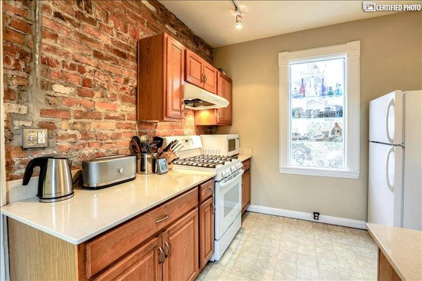 Exposed brick wall adds warmth to the kitchen