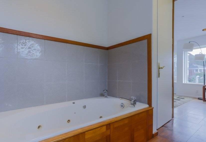 Long whirlpool bath tub with jets in bathroom
