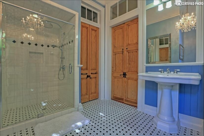 Light accents the huge master shower and enormous sink
