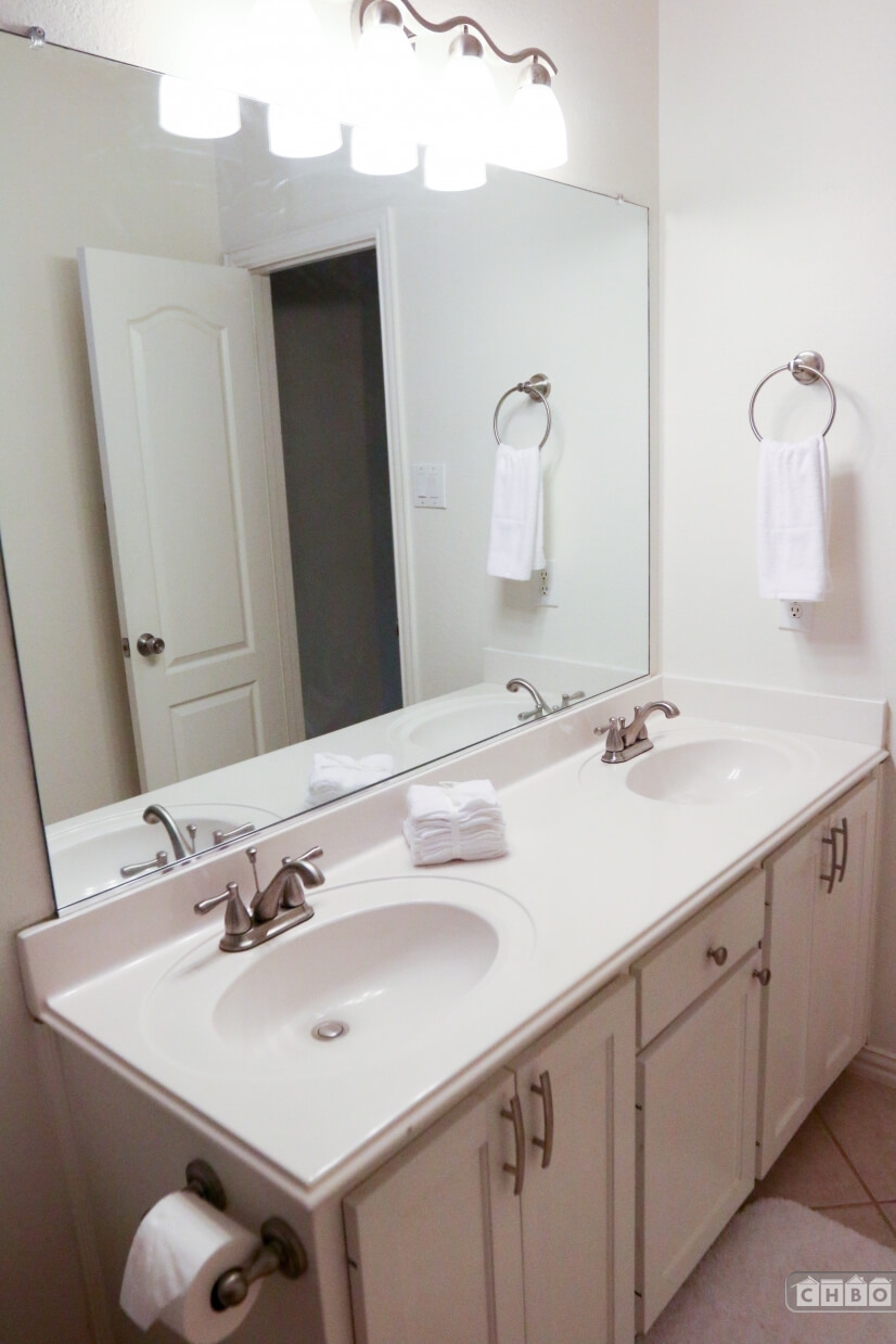 Guest bathroom has a double sink vanity