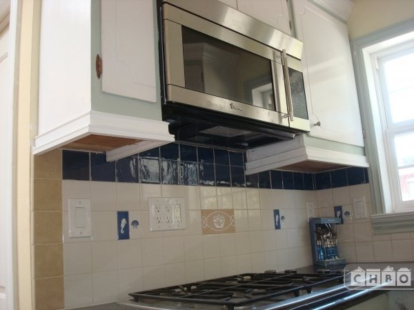 Kitchen with gas range and microwave