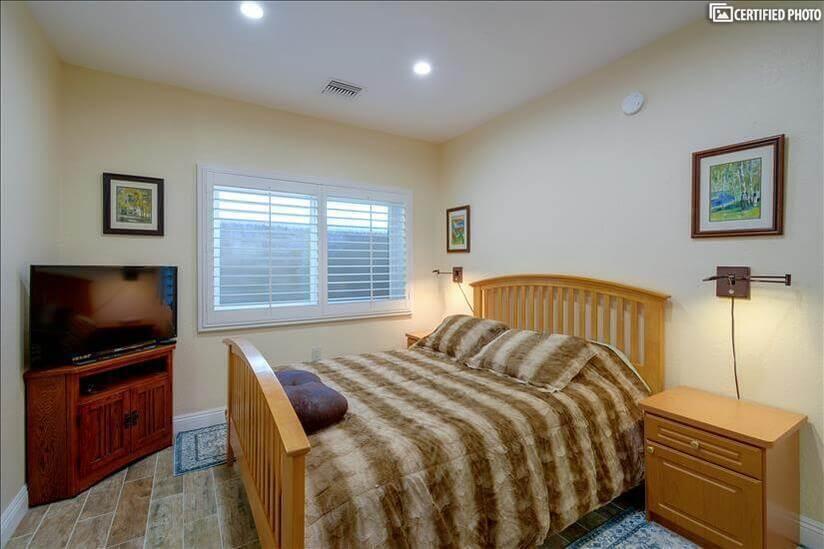 Flat screen TV and queen size bed in bedroom 2