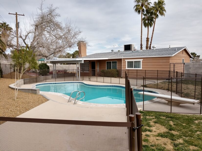 Backyard pool area with diving board & completely fenced in