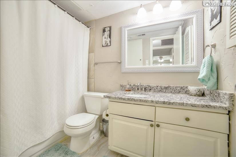 Combination tub & shower with a large mirror and vanity.