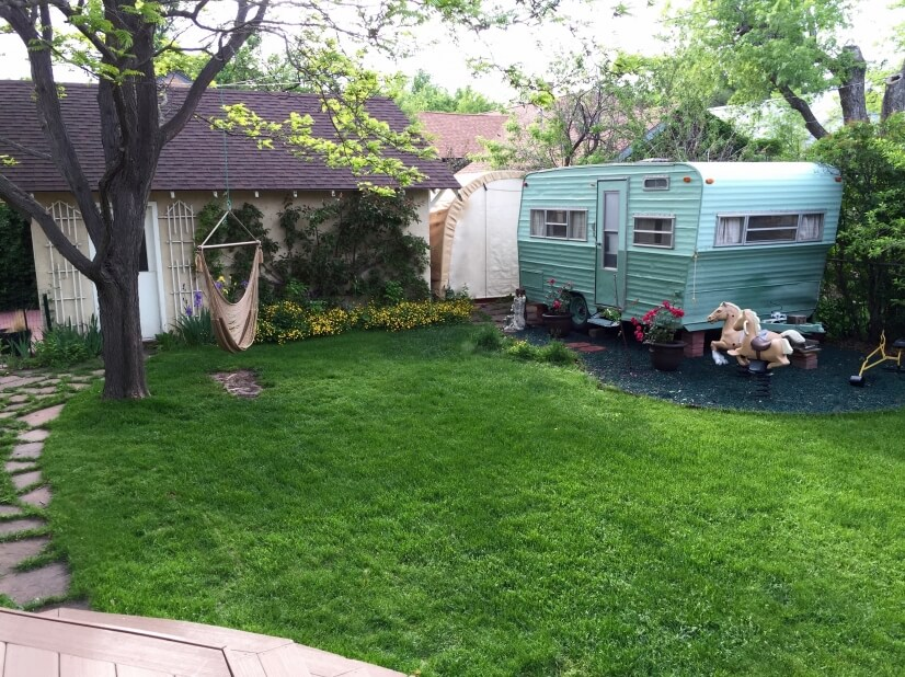 vintage camper in the back yard makes a great playhouse