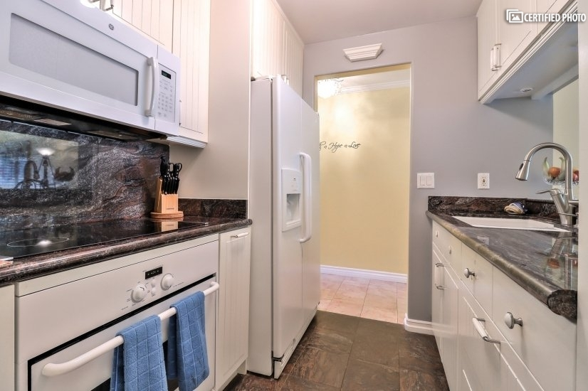 A fully equipped kitchen with granite counter tops.