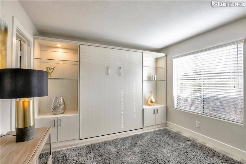 Custom cabinetry conceals guest queen bed