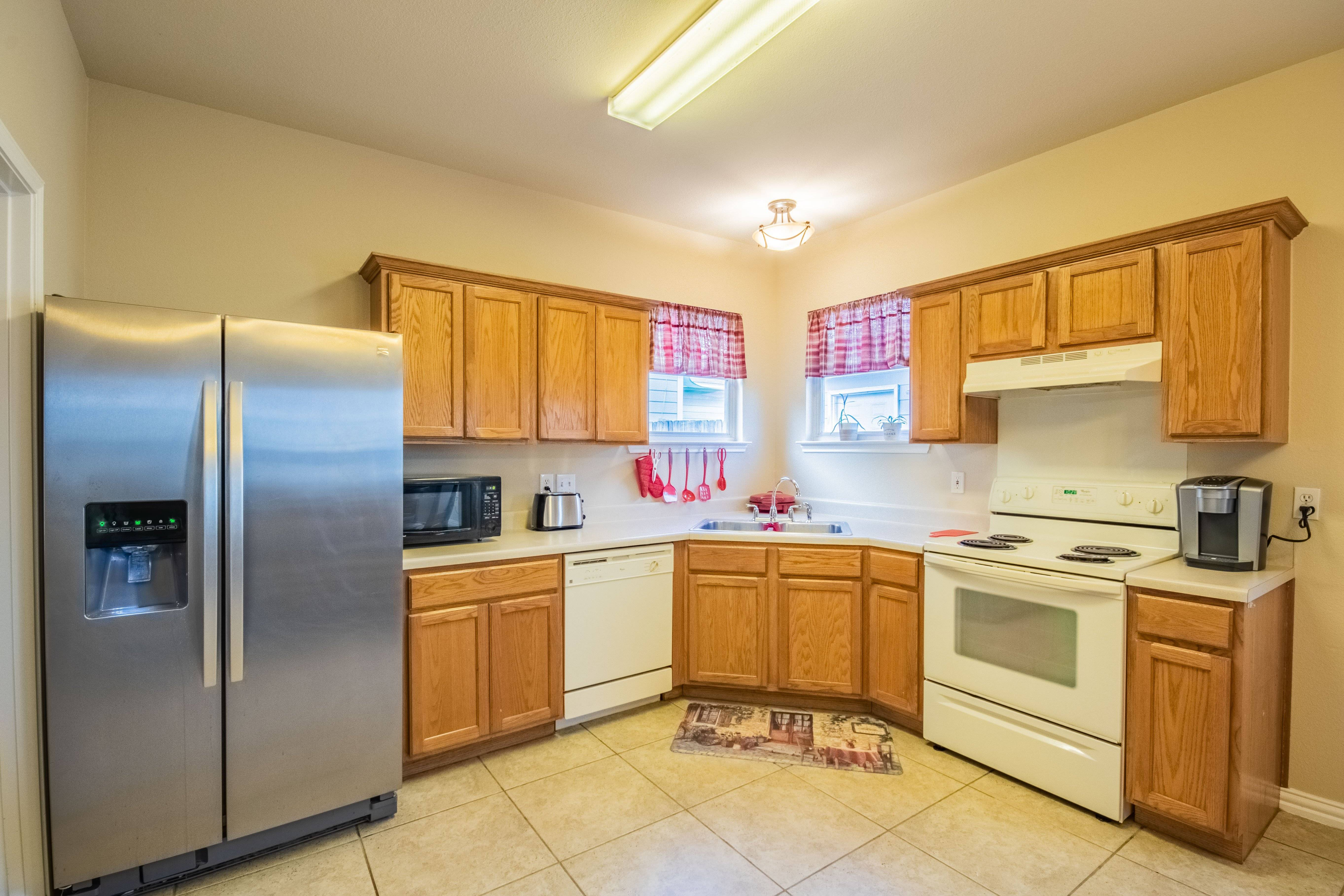 Fully equipped kitchen includes stainless steel refrigerator