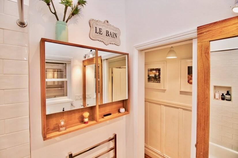 Custom bathroom includes teak wood details and large mirrors