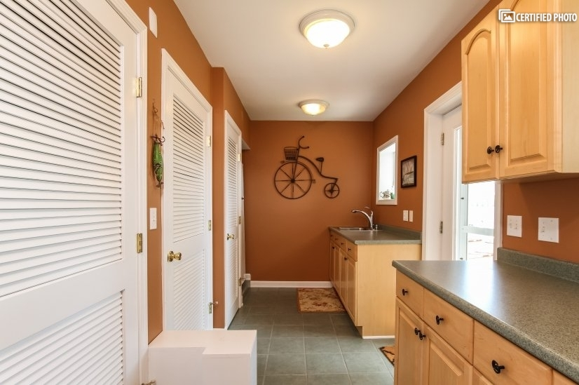 Opposite the full bath, this is a rear kitchen/utility area