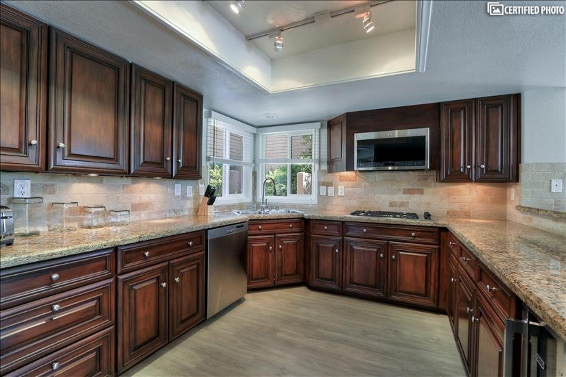 Warm Walnut finish kitchen cabinets with undermount lighting