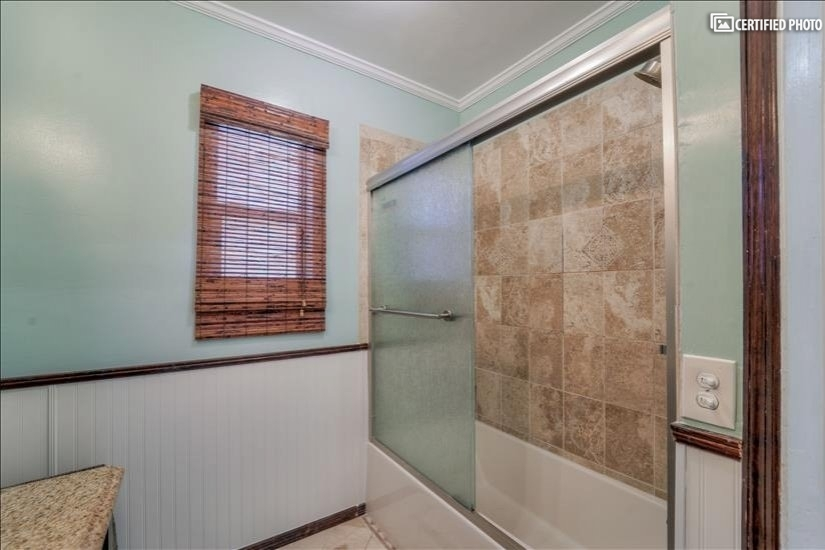 Soaking tub with glass doors.