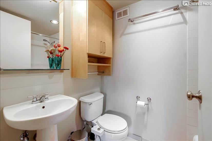Clean, tiled bathroom: storage, good lighting, bidet add-on.