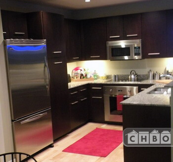 Rich dark cabinets, complimented with stainless rod pulls ad