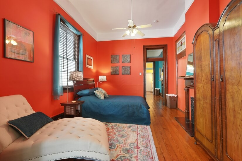 Master bedroom with queen bed, chaise, and armoire