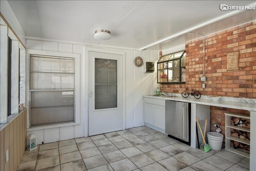 Sick and counter area. Door leading to Indoor sunroom.