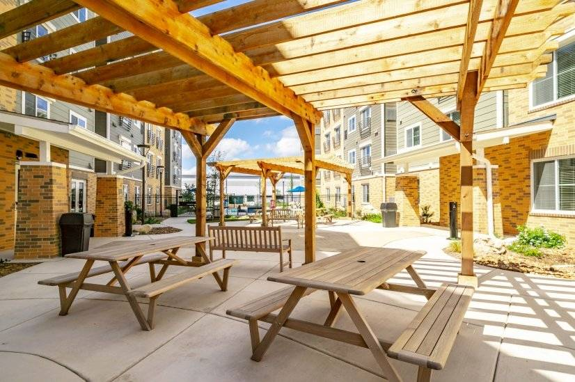 Outdoor patio area with gas grills and picnic tables.