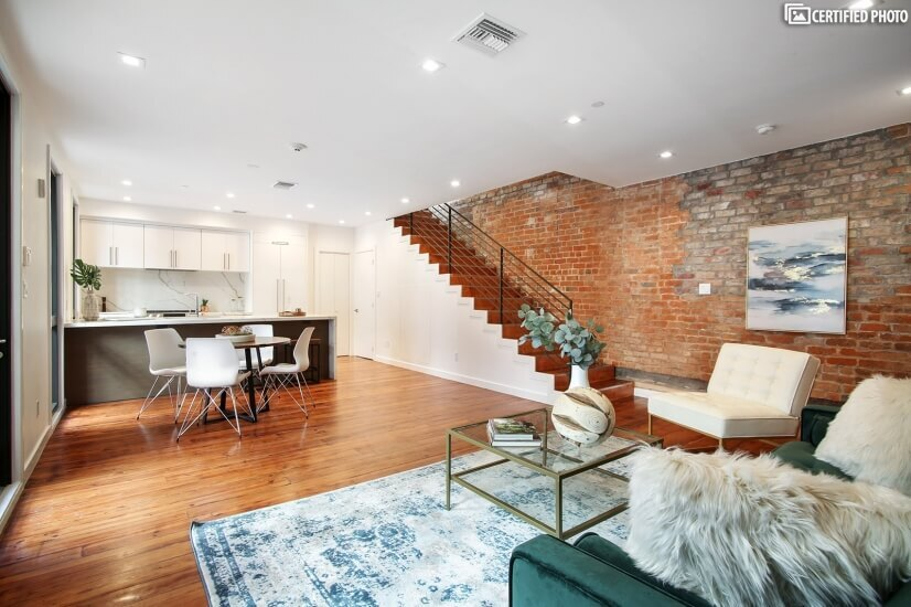 Open floor plan with original wood floors and exposed brick