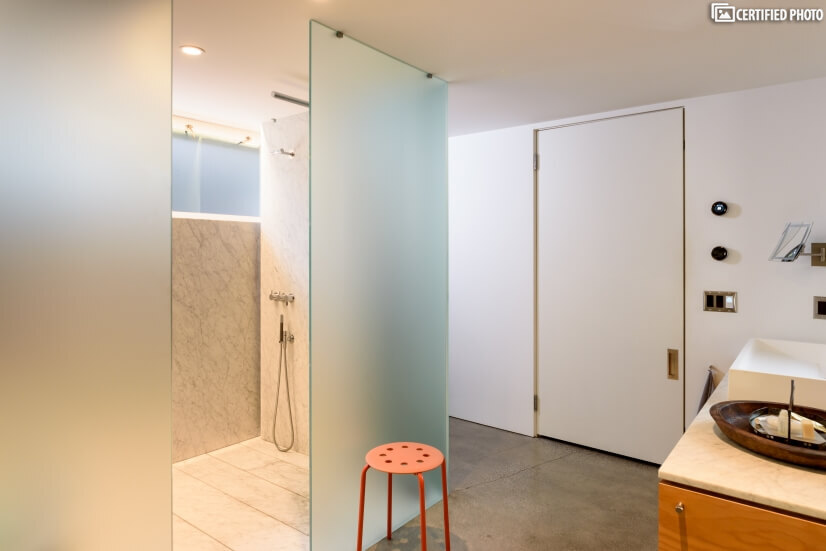 Walk-in Carrera marble wet room with a rainfall shower