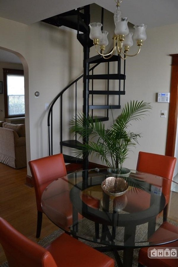 Dining area with feature spiral staircase leading to loft
