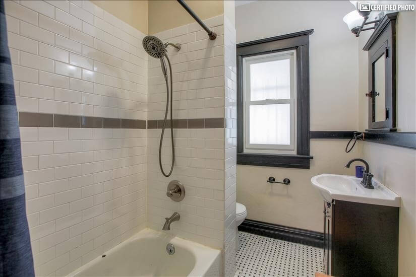 Classic white and black bathroom between two bedrooms