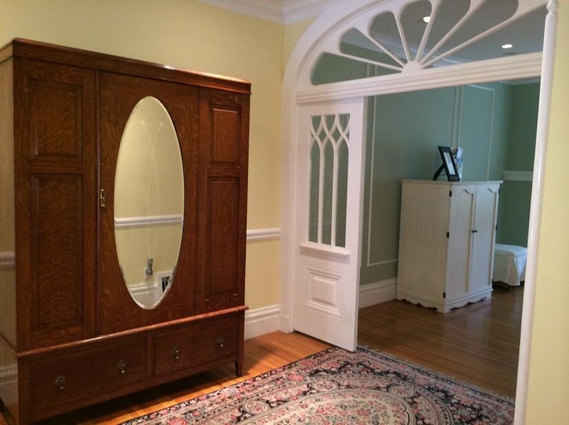 Entryway including antique armoire.