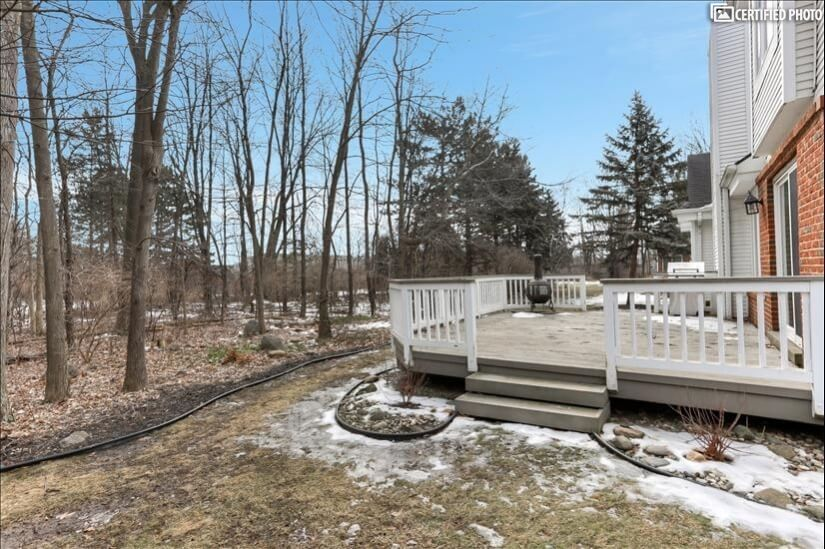 Outdoor deck sheltered by privacy of wooded lot.