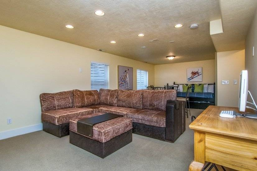Basement Family Room with sectional, dining table, bed