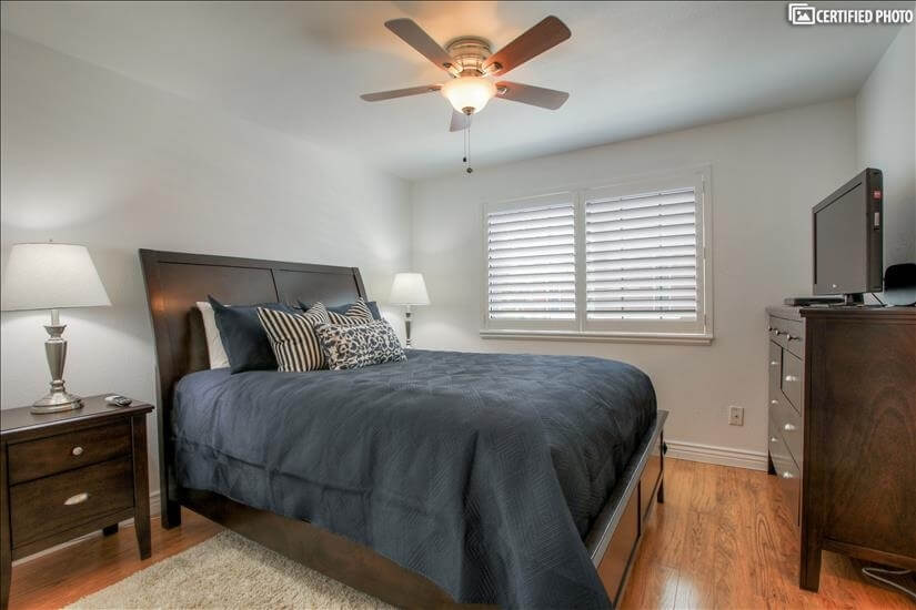 Master bedroom with fan and TV