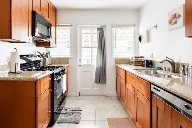 Kitchen with granite counterops, dishwasher, cooking utensil