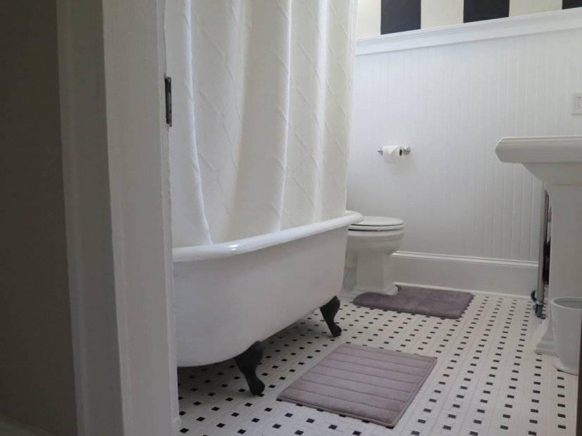Original 100+ year old clawfoot tub in bathroom.