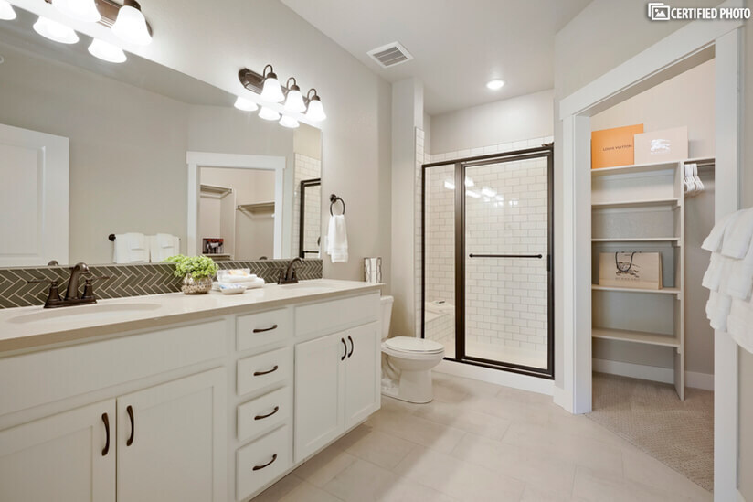 Master bathroom with double sinks and walk-in tile shower