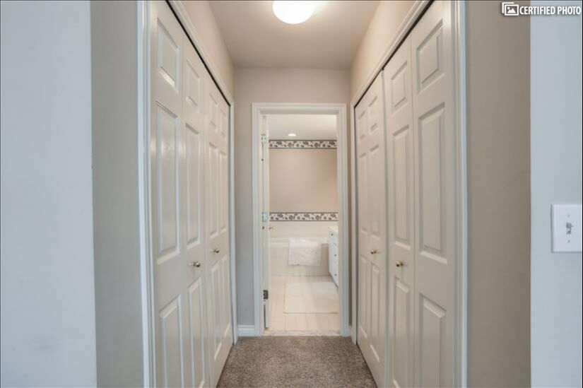 Master bedroom double closet hallway leading to bathroom.
