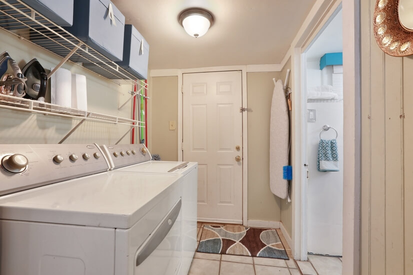 Laundry room with washer, dryer, and cleaning supplies