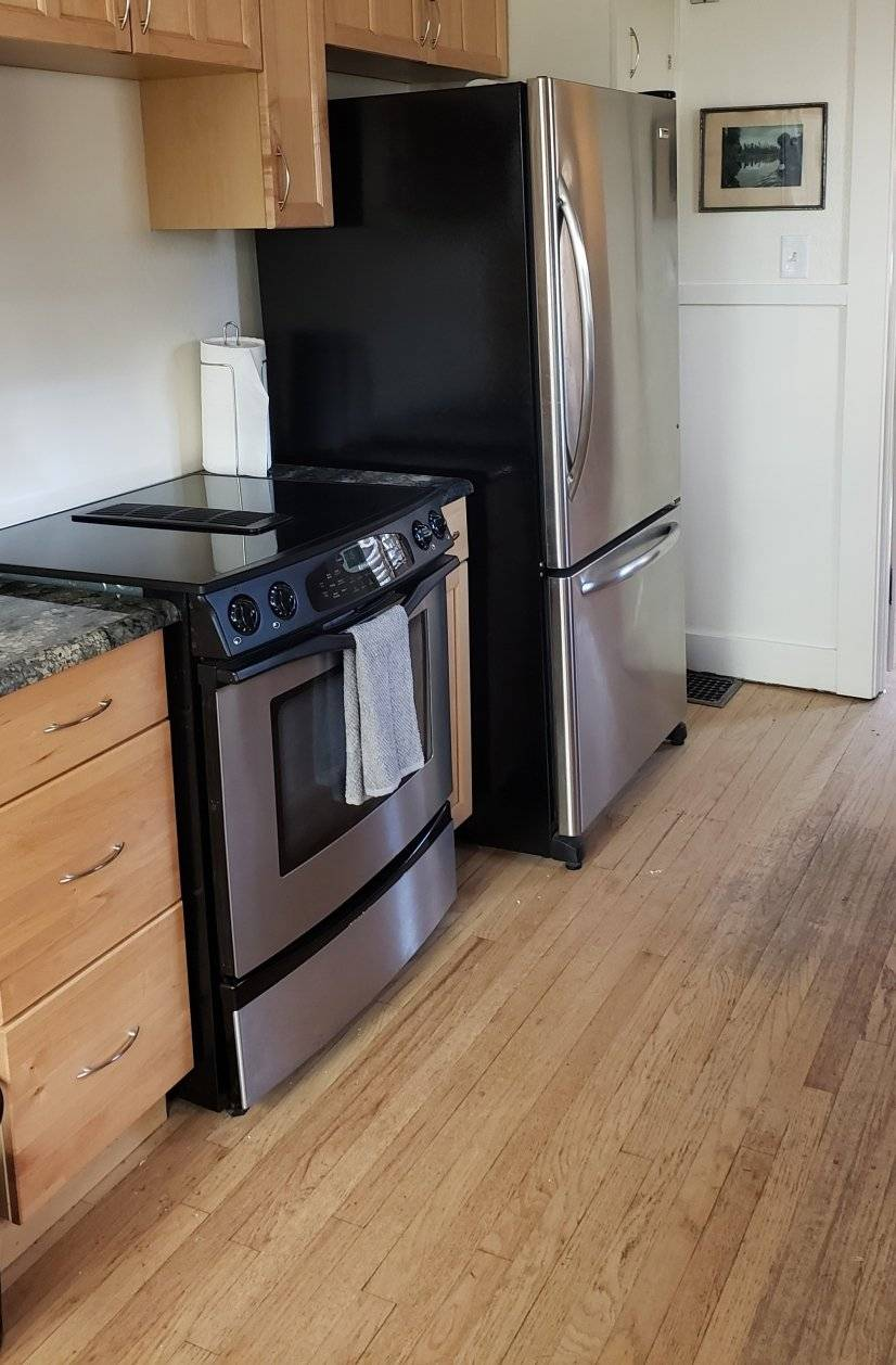 Other side of kitchen with stainless appliances and granite