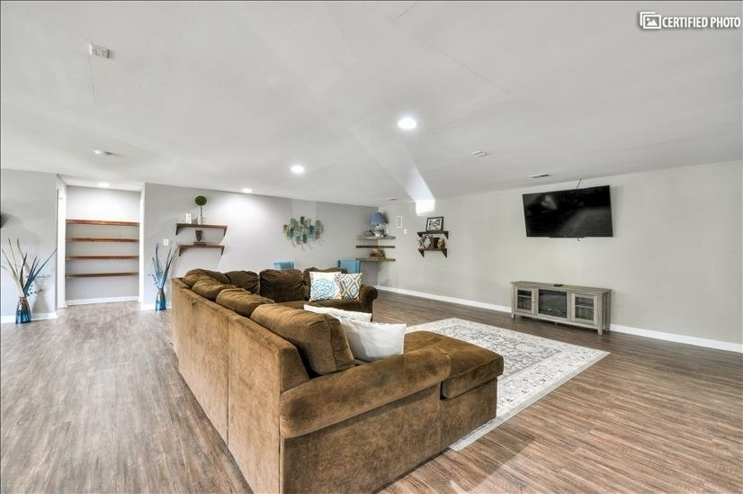 Large sectional with flat screen television over fireplace