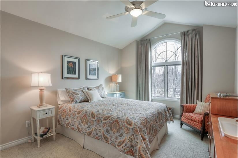 Sunny second-floor bedroom with high ceilings, large closet.