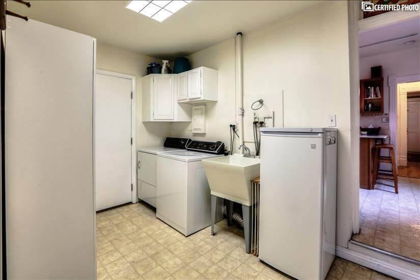 Mud room with laundry, storage, and freezer.