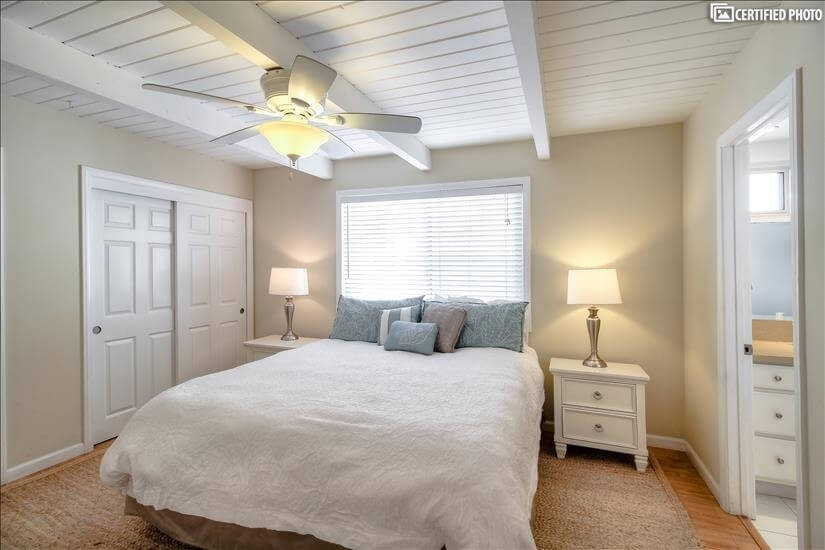 master bedroom with king bed and adjoining bathroom