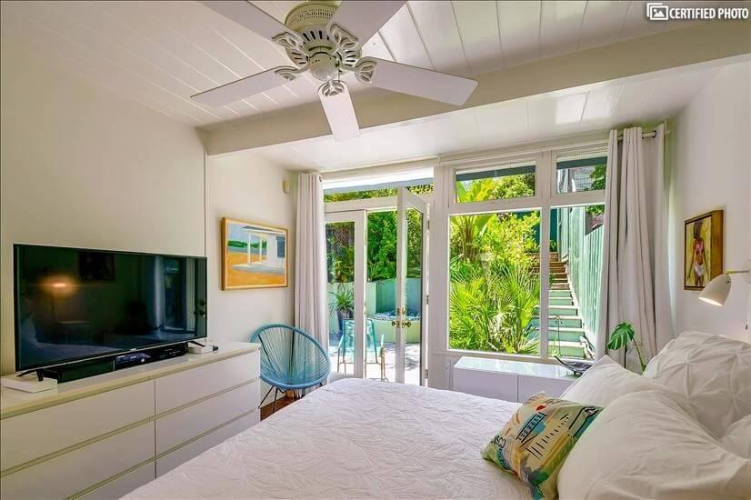 Ceiling fan, large flat-screen TV and padded headboard.