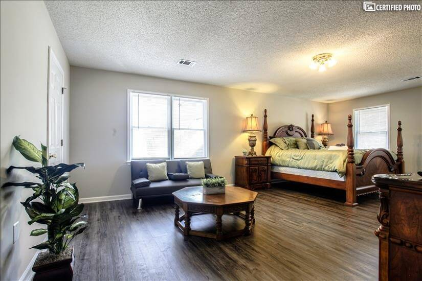 Large bedroom with sitting area on second floor of house.