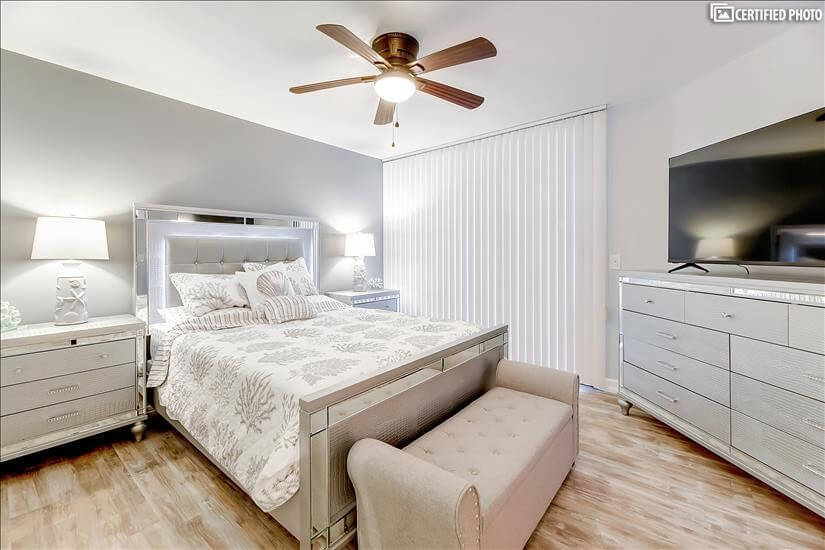 """Bedroom with 2 nightstands, dresser, and large 55"""" TV"""