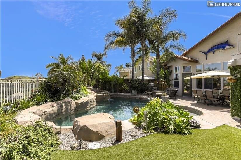 View of the pool, jacuzzi, patio area, fire pit & barbecue.