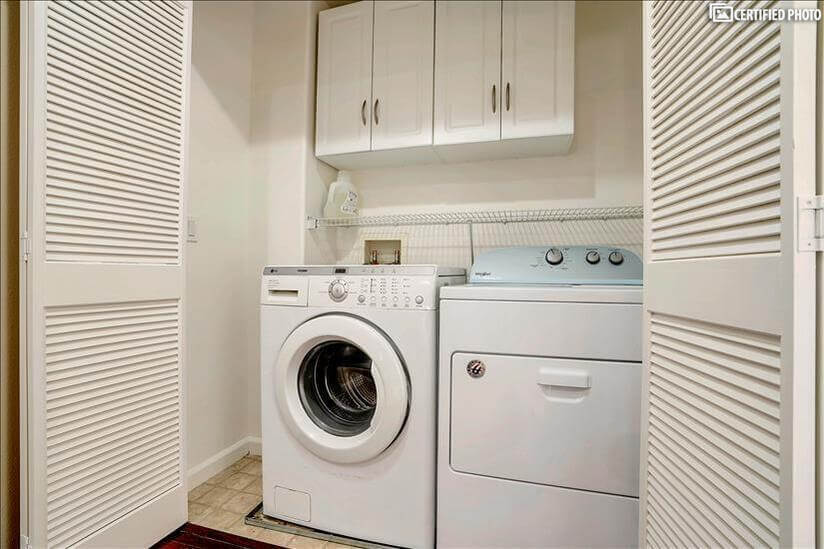 washer and Dryer room with storage cabinets a