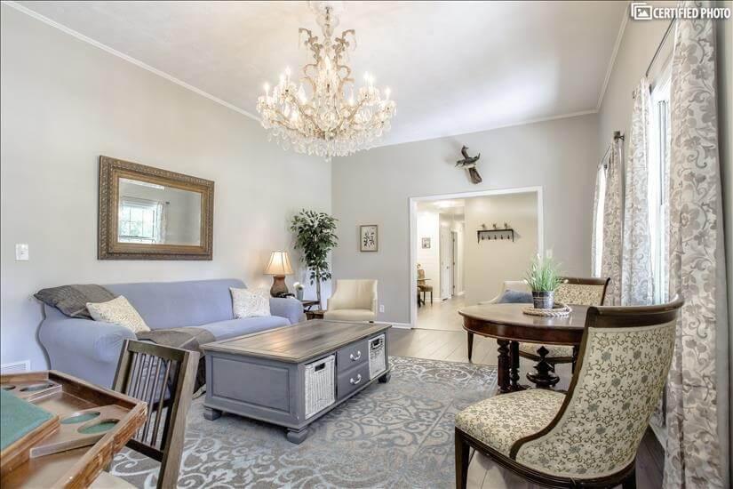 An elegant light filled room and chandelier c