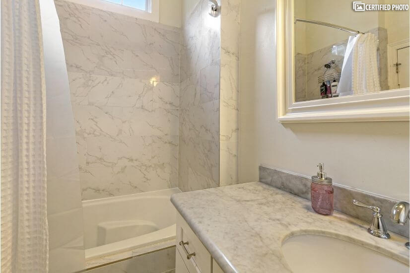 Master bath room with large tub and shower with marble tile