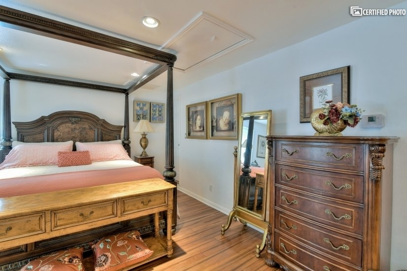 King size bed and chest with entrance to closet.