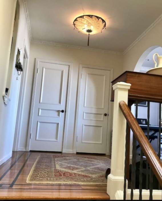 Laundry and coat closet in entryway, with inlaid wood floors