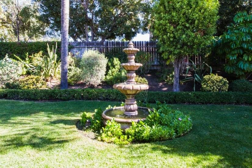 Tranquil fountain with on/off switch in kitchen, grass lawn
